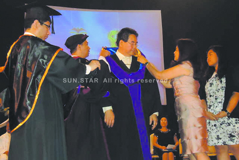 BACOLOD. Congressman Rufus Rodriguez (center) dons the hood and cap during the conferment of his Doctor of Laws (Honoris Causa) at UNO-R on Thursday. (Carla N. Cañet) `