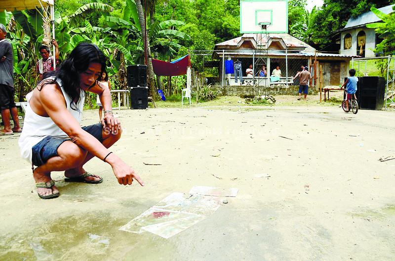 CEBU. A man points to the spot where Carcar City Mayor Nicepuro Apura's son, Carl Vinson, 25, was shot dead early Sunday, during a concert in Barangay Valladolid, Carcar. (Amper Campaña)