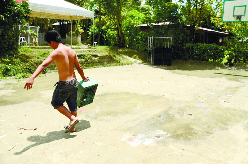 CEBU. A resident passes by the spot (covered by paper) where Carl Vinson Apura, 25, was gunned down during a fiesta concert in Sitio Upper Tubod, Barangay Valladolid in Carcar City. (Amper Campaña)