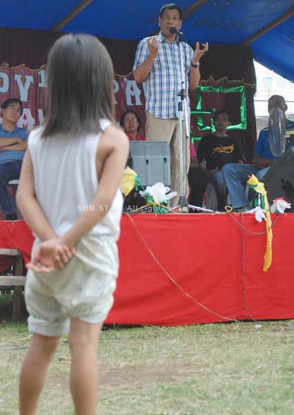 DAVAO. A young girl intently listens as acting Mayor Rodrigo Duterte delivers a message during the Araw ng Barangay 36-D celebration on Wednesday afternoon. Duterte called on parents to be responsible, to take care of their children and provide them with proper education. (King Rodriguez)