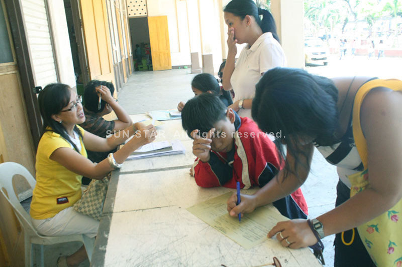CAGAYAN DE ORO. Teachers at the City Central School attend to parents and pupils who submit their credentials for enrolment on Monday. (Joey P. Nacalaban)
