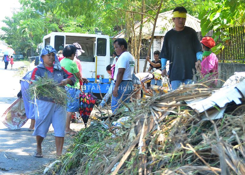 """DAVAO. Mga molupyo sa Barangay 10-A Poblacion, siyudad sa Davao nanglimpyo sa drainage sa ilang pag-apil sa """"Food for Work"""" niadtong Martes sa dakbayan sa Davao. (Seth Delos Reyes)"""