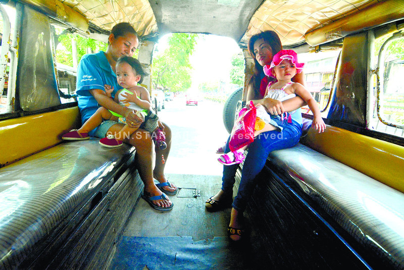 MOTHER'S DAY. Two mothers hold with their child while riding on a PUJ bound to Cebu City. <br /> foto: Alex Badayos