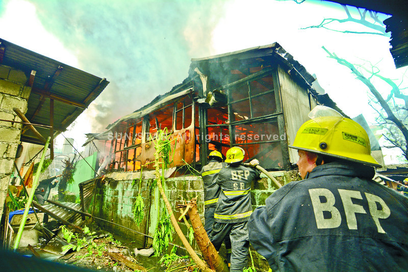 Firefighters hold back the flames that hit a compound in Sitio Esco, Barangay Guadalupe, Cebu City. Some residents saw sparks from outside the compound, but investigators have yet to confirm how the fire started. Esco stands for Englis-V. Rama Social Circle Organization. (Sun.Star Cebu/Alex Badayos)