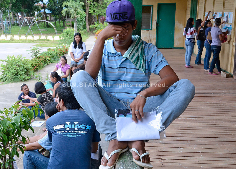 DAVAO. A poll watcher takes a rest while others hang around by the stairs of the Catalunan Grande Elementary School Monday waiting for the Comelec representative in the testing and sealing of the PCOS machines at the clustered polling places. (King Rodriguez)