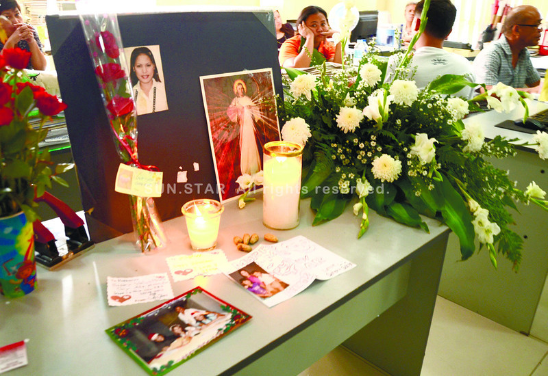 "CEBU. The desk of Rohamma Luage at the division for the welfare of urban poor (DWUP) is laden with flowers and condolence notes. The roses wrapped in plastic were said to have been given to Luage by Mabini Barangay Captain Rey Oybenes last Thursday and bore a card that said ""I love you, goodbye."" (Ruel Rosello)"