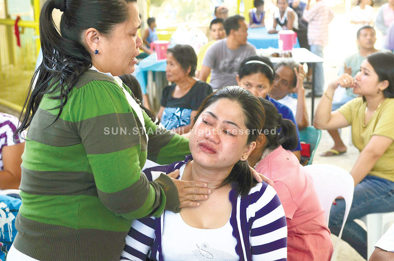 A relative comforts Jecebel Oybenes (seated), widow of Mabini Barangay Captain Rey Oybenes, who allegedly killed a woman before shooting himself. Rey's wake is held at the barangay sports complex. (Arni Aclao)