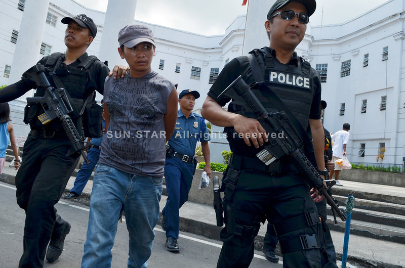 Members of the Cebu Provincial Police Special Reaction Unit escort a handcuffed Joavan Fernandez after appearing before the Provincial Prosecutor's Office, which filed additional charges against Talisay Mayor Socrates Fernandez's adopted life. (Sun.Star Cebu/Amper Campaña)