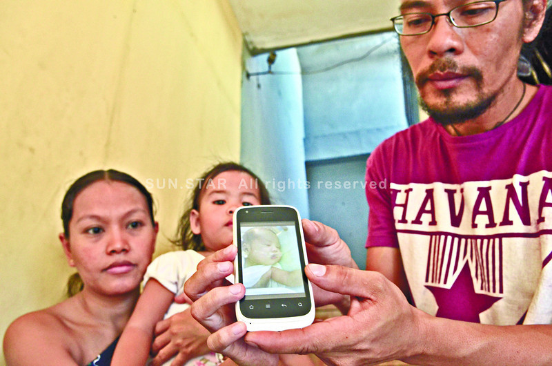 TAPED. Ryan Noval (right) shows a picture of his child whose mouth was taped inside a maternity hospital.With him is his live-in partner Jasmine<br /> Badocdoc (left) and their two-year-old daughter. The couple posted the photo on Facebook and attracted the attention of netizens.<br /> (SUN.STAR FOTO/AMPER CAMPAÑA)