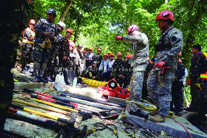 THE TOOLS AND TRAINING OF EMERGENCY HEROES. Soldiers and civilian rescue volunteers gather around some equipment they'll use in rescue operation drills, as part of the Philippines-US Balikatan Urban Search and Rescue Exercises 2014 in the military's Central Command in Cebu City. (SUN.STAR FOTO/ALLAN DEFENSOR)