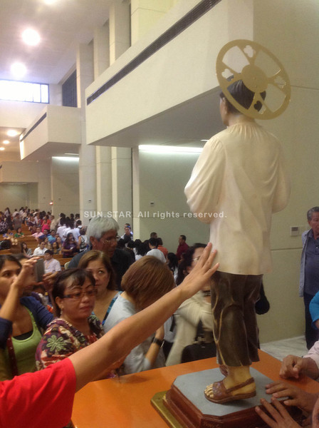 CEBU CITY. People line up to wipe the pilgrim image of San Pedro Calungsod at the South Road Property (SRP) Thursday afternoon. (JAC)
