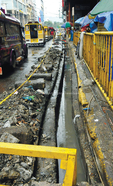 DRAINAGE WOES. Works to improve drainage at the downtown area of<br /> Osmeña Blvd. stop for the weekend. Flooding in the downtown area has<br /> always been a headache to commuters and motorists. (Arni Aclao)