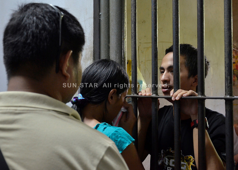 DAVAO. 'Baktin Yu' carnapping syndicate member Mark Zapanta Daquiado wears a faraway look in his eyes as he contemplates the offer of his lawyer to bail him out, while Daquiado's wife sobs. (King Rodriguez)
