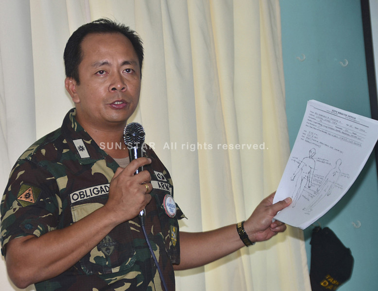 DAVAO. Maj. Jake Obligado shows a copy of the autopsy report on four soldiers who were killed in an ambush staged by suspected New people's Army rebels in Mapula, Paquibato district last November 5. (Seth Delos Santos)