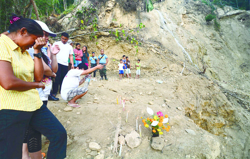 EMOTIONAL DEBRIS. On All Saints Day, Prima Empinado lights candles, places flowers and offers prayers for the souls of her eight- and 10-year-old children and three other kids who were buried in a landslide at the Buyong Falls in Katipunan, Sagbayan during the 7.2 magnitude earthquake that hit Bohol on Oct. 15. (Alex Badayos photo/Sun.Star Cebu)