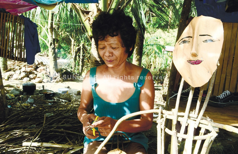 CEBU. Marina Ayuda (right), mother of 10, uses mainly natural materials to make Christmas decor, like the parol (above) that is made of corn husk, guinit and twigs. She also makes nativity scenes and Christmas trees. Her roadside store enjoyed robust sales with the steady traffic of vehicles carrying relief goods to northern Cebu towns affected by super typhoon Yolanda. The typhoon also damaged Ayuda's roof. After Christmas, Ayuda returns to making woven baskets for export companies in Liloan and Mandaue City. (Allan Cuizon/Sun.Star Cebu)