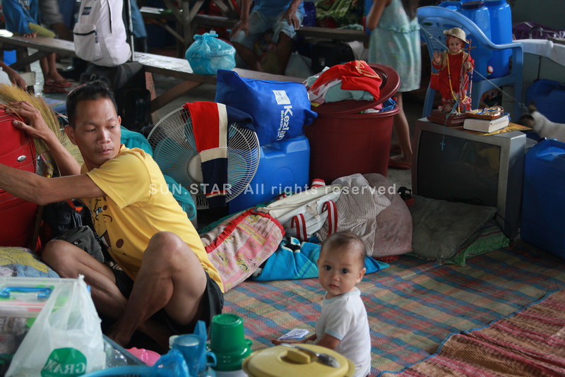 This father and his child are among the residents of Barangay Macasandig, Cagayan de Oro City to evacuate early at Macasandig evacuation center on Thursday. (Cai D. Panlilio)