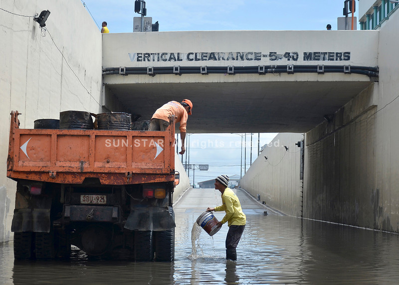 DAVAO. With no sump pump to speak of, a worker of the Department of Public Works and Highways uses a pail to gather floodwater and haul this up to a dumptruck loaded with empty barrels at the Buhangin underpass. (King Rodriguez)