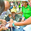 SENIOR PRIVILEGE. A relative helps a senior citizen leave a thumbprint on a form to confirm his receipt of P2,000 from the Cebu City Government in the Barangay Luz Elementary School. (Amper Campaña photo/Sun.Star Cebu)