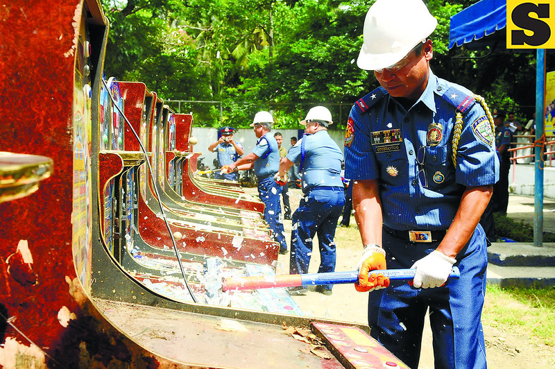 CEBU. Chief Supt. Danilo Constantino, Central Visayas police director, leads the destruction of more than 200 gambling machines confiscated by the police, in a ceremony held on the Cebu Provincial Police Office grounds. (Arni Aclao photo/Sun.Star Cebu)