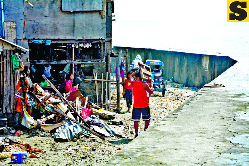 CEBU. A family tries to pick up the pieces, after a surge battered their home in Litmon, Dumlog, Talisay City. (Alex Badayos photo/Sun.Star Cebu)