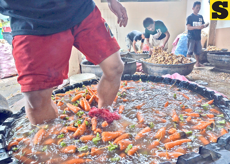 FASTER THIS WAY. A laborer uses his feet to churn water that removes the mud from carrots inside the vegetable section of the Bankerohan Public Market. Behind him, workers clean ginger. (King Rodriguez)