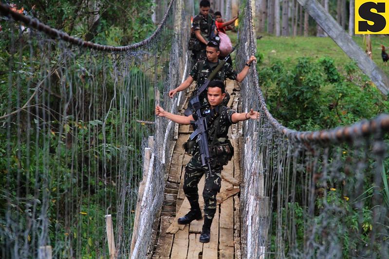 Soldiers crossing a hanging bridge