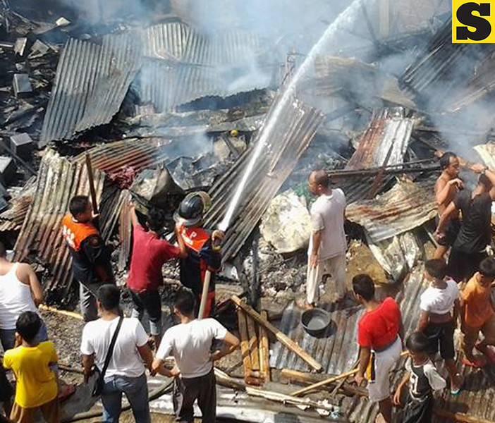 BASILAN. A fireman extinguishes the fire that razed 15 business establishments and 18 houses in Isabela City, Basilan on Wednesday. (Bong Garcia)