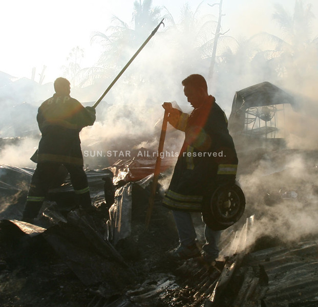 ZAMBOANGA. Firemen sift through the debris after containing a fire that hit a slum area in a west coast village of Zamboanga City on Wednesday. (Bong Garcia)