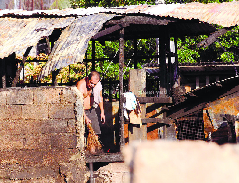 AFTERMATH. A fire victim in Barangay Day-as, Cebu City tries to clean what was left of his house after a blaze hit the area past noon last Wednesday. (Sun.Star Photo/Allan Cuizon)