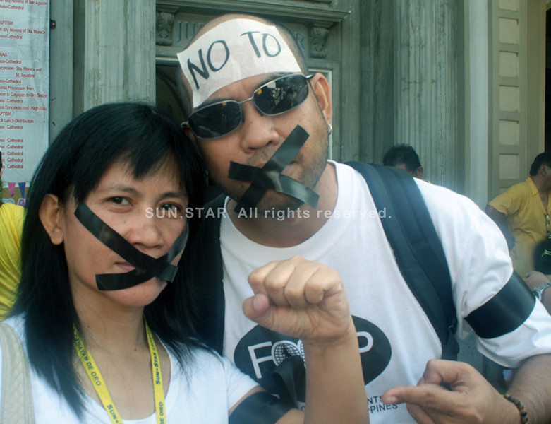 CAGAYAN DE ORO. Two journalists in Cagayan de Oro show off their disgust to the newly-passed Cybercrime Prevention Act by taping their mouth as the new law is believed to gag the media's freedom of speech and expression. (Joey P. Nacalaban)