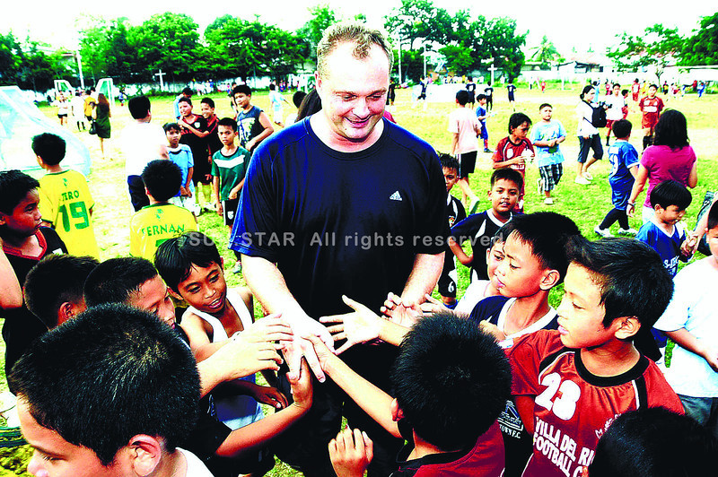 BRIEF VACATION. Young players gather around Hans Michael Weiss during an earlier visit to Cebu. The Philippine coach is back for a brief vacation with his family and he took the chance to inspect the Cebu City Sports Center. (Sun.Star File)