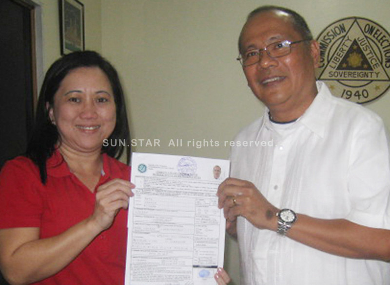 BACOLOD. Atty. Lyndon Caña, with Bacolod Comelec officer Mavil Majarucon-Sia, shows the certificate of candidacy he filed on Thursday, October 4, 2012. (Carla N. Canet)