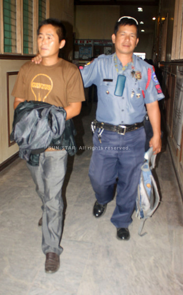 CAGAYAN DE ORO. Chinese national Zong Hengyuan is being escorted by a policeman during Monday's inquest at the city prosecutor's office. (Joey P. Nacalaban)