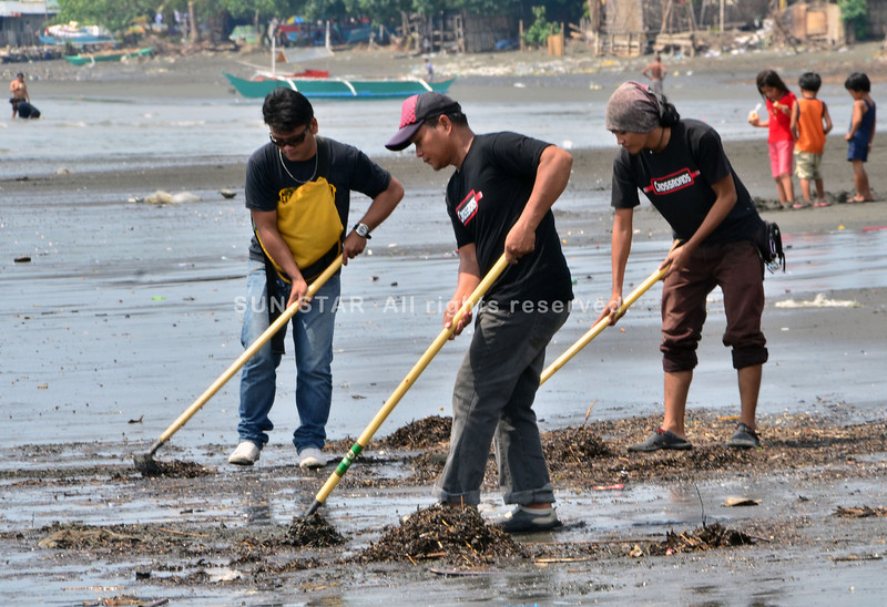 DAVAO. Members of the Crossroads Motorcycle Riders participate in a coastal clean-up on the shores of Bucana, Barangay 76-A as part of their community services program Sunday. (Seth Delos Reyes)