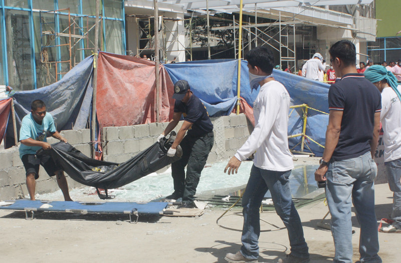 The body of Ramil Mugot hours after he was pinned down by bulk of fiber glasses while trying to unload from a cargo truck to be delivered to the ongoing construction site at Centrio Ayala, yesterday morning. Two others were seriously injured and were brought to the nearest hospital (PHOTO BY JOEY P. NACALABAN)