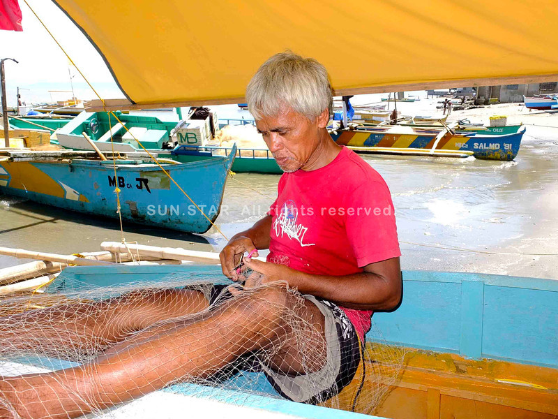 CAGAYAN DE ORO. Fisherman Antonio Amancio cut the silvery nets inside his 15-footer pump boat docked on the sands in Barangay Bonbon on Saturday, September, 14, 2013. He came home from fishing without a catch on Friday evening. (Bobby E. Lagsa)