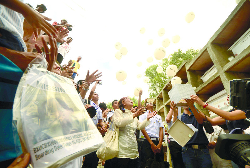 CEBU.Balloons and butterflies are freed after a mass burial in Cebu City's Carreta cemetery. The families of the 46 are still waiting for the authorities to confirm their loved ones' identities.(Ruel Rosello)