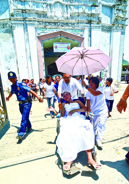 CEBU. Paramedics escort Beatriz Largo-Sayloon from a mass wedding in the St. Francis of Assisi Parish in Naga City to a clinic just across the street, where she gave birth to a girl. Mother and baby are both safe. (Alex Badayos photo of Sun.Star Cebu)