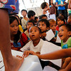 CAGAYAN DE ORO. Children in a day care center inside the Zamboanga City Sports Complex, temporary home to more than 44,000 family evacuees from the six barangays affected by the fighting, listen as another child stands on a chair to explain and show his drawing. (JB R. Deveza)