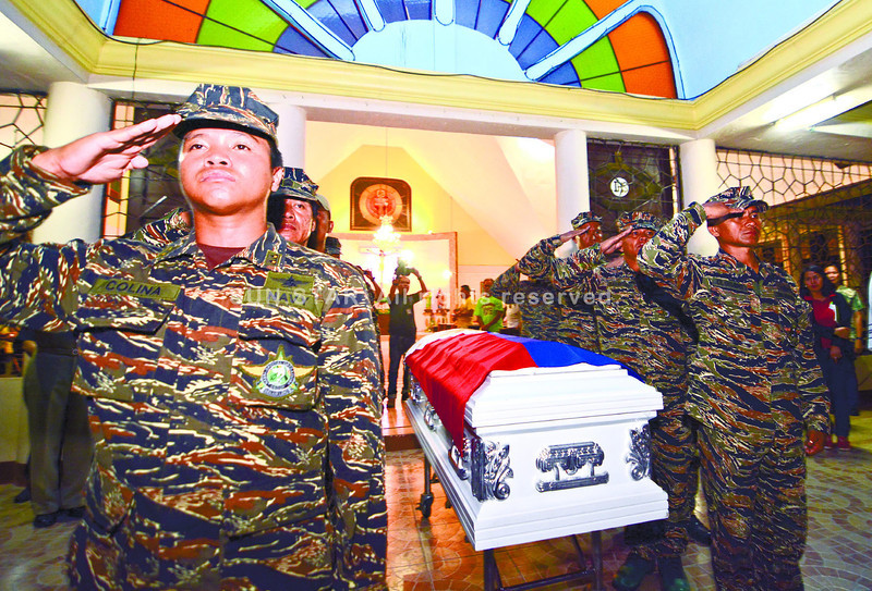CEBU.Colleagues in Cebu flank the coffin of Naval Forces Petty Officer 3 Jose Audrey Banares, a father and husband who died during an encounter between soldiers and the Moro National Liberation Front. He is a survived by his wife of 17 months and their baby, who will turn three months old soon. (Alex Badayos)