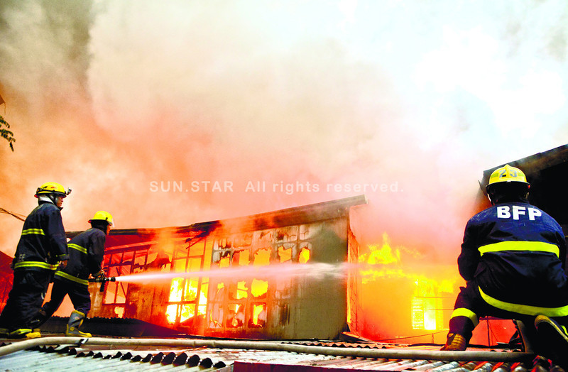 Fireman battle the fire that burn several houses in Brgy. Kamagayan at the back of the Barangay hall.<br /> foto: Alex badayos