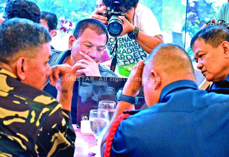 DAVAO. Si Davao City Mayor Rody Duterte naglantaw sa hulagway nga nakuha sa bomb squad human mibusikad ang duha ka bomba sa sinehan sa Gaisano Mall ug SM City Davao atol sa command conference nga gipatawag sa mayor didto sa Grand Menseng Hotel. (King Rodriguez)
