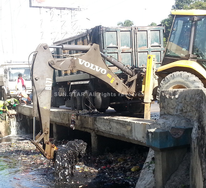 CAGAYAN DE ORO. A city government-owned backhoe scoops tons of garbage that gathered in Bitan-ag Creek along Claro M. Recto Avenue. (Joey P. Nacalaban)