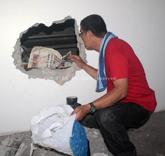 CAGAYAN DE ORO. A Scene of the Crime Operative examines the hole where the suspects gain entry inside the Asian Hills Bank in Carmen, Cagayan de Oro. (Joey P. Nacalaban)