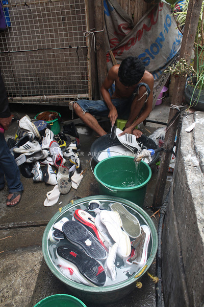 CAGAYAN DE ORO. A man cleans used shoes intended to be marketed at major streets in Cagayan de Oro. Tens of used clothing peddlers earn thousands of pesos from recycled used clothing. (Joey P. Nacalaban)