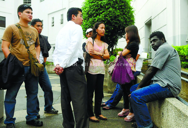 Papua New Guinean Bennidict Penini(right) sits outside the Palace of Justice with his friends and lawyer Atty. Fritz Lastimoso(3rd left) together with S.W.A.T. policemen PO1 Philip James Tanza(left) and PO2 Bradford Lavandero(2nd left) after the filing of the case against the foreigner 10Sep2012.                                                                                       (SUNSTAR FOTO/ARNI ACLAO)