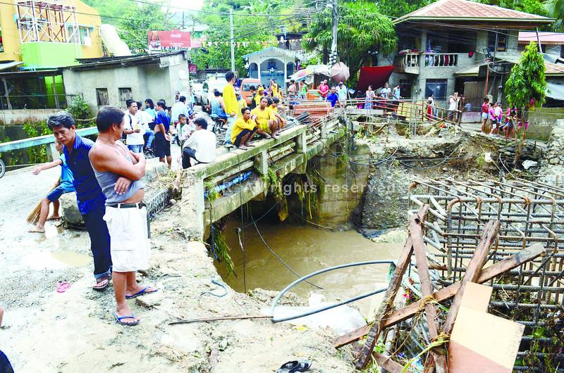 SAPANGDAKU, LITERALLY. Residents keep a wary eye on the rising water under the Sapangdaku bridge in Cebu City. (Ruel Rosello)