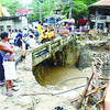 SAPANGDAKU, LITERALLY.  Residents keep a wary eye on the rising water under the Sapangdaku bridge in Cebu City.  (Ruel Rosello)