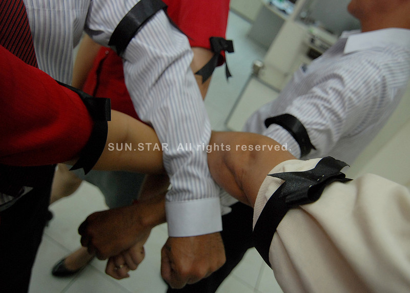 DAVAO. Several officers of the Development Bank of the Philippines show their black armbands as a show of protest against the withholding of their benefits. (King Rodriguez)